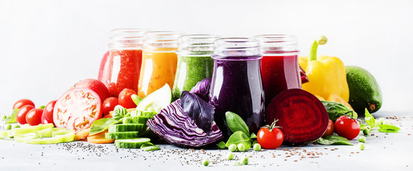 Food and drinks, selection of healthy and useful colorful vegetable juices and smoothies with chia and flax seeds in glass bottles, set on gray background, selective focus