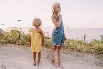 Two little sisters on the path to the sea