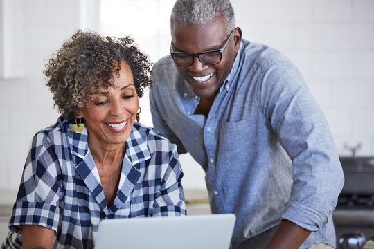 Senior African American couple using a computer in the kitchen together