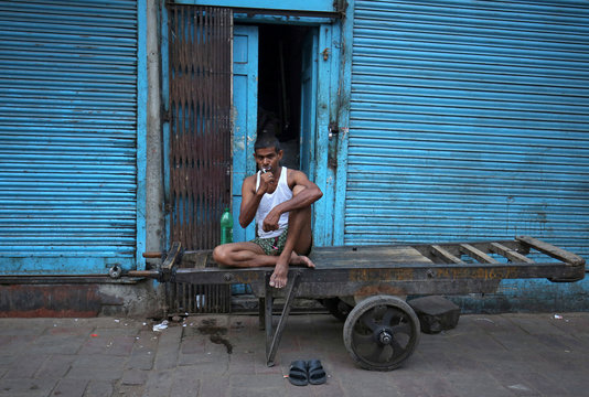 A labourer brushes his teeth as he sits on a handcart in a market area in the old quarters of Delhi