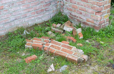 Broken wall, bricks on the ground