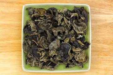 Dried Chinese edible black fungus, called Jew's Ear Mushroom in green dish, top view