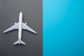 Flat lay airplane on grey and blue background
