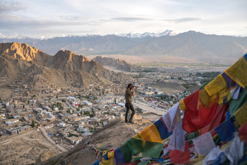 Man standing on peak and taking pictures with camera of desert village surrounded by mountains