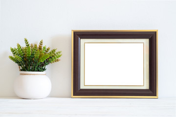 Blank picture frame on white table and white wall