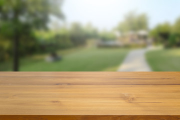 Empty wood table top against blurred green nature and tree background