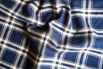 Textile background with a checkered blue napkin, top view. Natural textile background. Fabric texture background. Texture of natural linen fabric.
