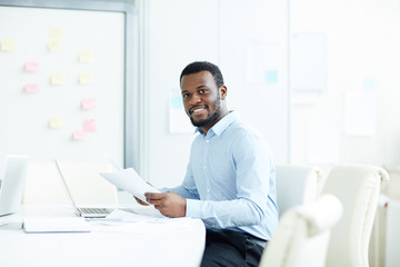 Portrait of African American young businessman working with documents at office desk and smiling at camera