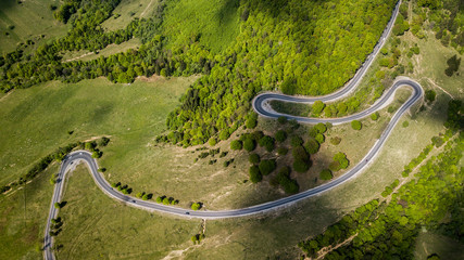 Winding road from high mountain pass, in spring time. Aerial view by drone . Romania