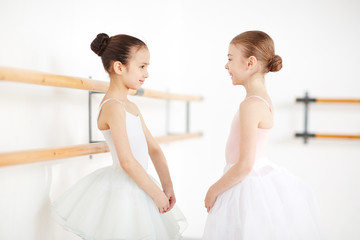 Young ballerinas with strict hairstyle staying and smiling in white room with sunlight