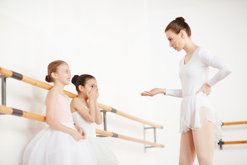 Young girls in white tutu listening pedagogue in short dress with emotions in light dancing studio