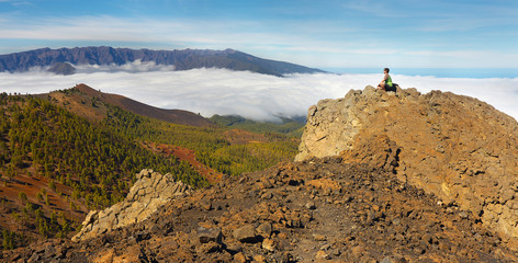 Man sitting on the rock watching a volcanic landscape with a Caldera de Taburiente on background, island of La Palma, Canary Islands, Spain
