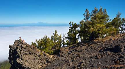 Man sitting on the rock watching a volcanic landscape with a mountain of Pico de la Teide on background, island of La Palma, Canary Islands, Spain