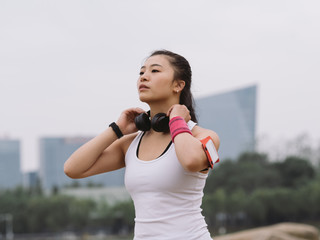 portrait of sporty woman standing at lakeside with a black headphone on her neck