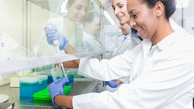 Group of scientists in research laboratory working under splashback