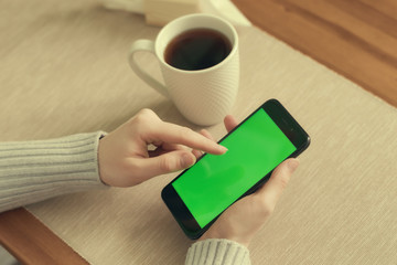 Woman hand holding mobile phone, She using in mobile applications and multimedia programs.