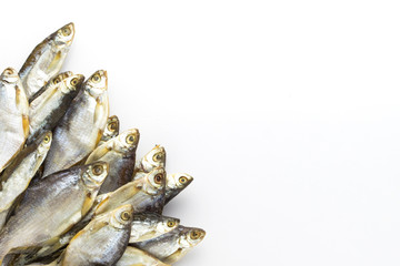 Dried fish lined in the lower left corner on a white background. Flat lay, top view