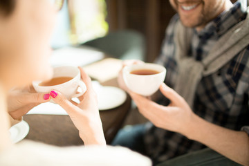 Two crop people sitting in cozy cafe and enjoying aromatic tea during business meeting.