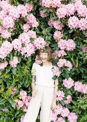 Portrait of girl laughing in pink flower bush
