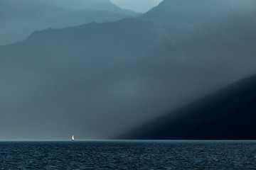 A distant sail boat being lit up by a beam of light passing through the mountains