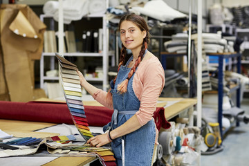 Confident Worker Holding Fabric Swatches In Sofa Workshop