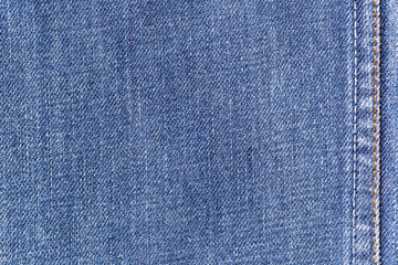 Denim jeans fabric texture background with seam for clothing, fashion design and industrial construction concept.