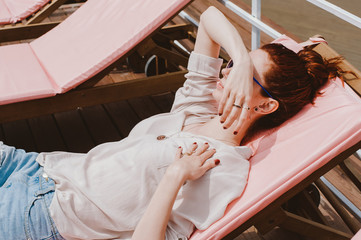 Woman lying on a pink chaise lounge