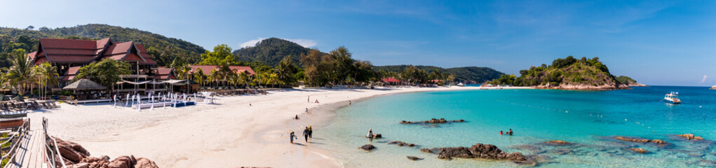 Beautiful panoramic view of Long Beach (Pasir Panjang) on Redang Island in Terengganu, Malaysia. Tourists enjoying their leisure time along the white powdery sand beach and crystal clear blue water. Wall mural