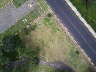 Young woman laying on the grass in the park in summer - view from the drone