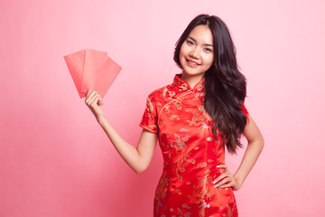 Cute Asian girl in chinese red cheongsam dress with red envelope