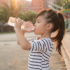 Child drinking pure water in park