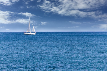 White modern yacht sailboat sailing alone on calm blue sea waters on a beautiful sunny day with blue sky and white clouds.