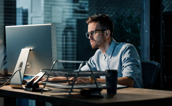 Young focused man doing overtime job watching computer at desktop in dark office.