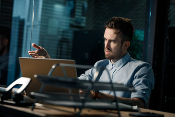 Misunderstanding adult man sitting at laptop and pointing with hand in the office.