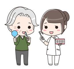 シニア男性に歯磨き指導をする歯科衛生士の女性(全身)
