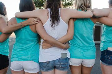 young women with arms around each other backs to camera