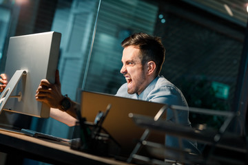 Man looking furious and screaming at computer having problems with work and connection