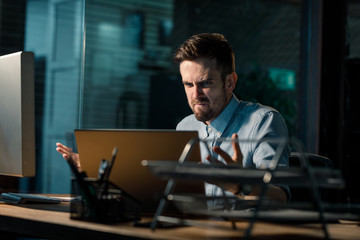 Casual man working in office and looking super mad having problems with malfunctioning laptop in office