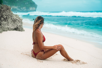 Girl Brunette with curly hair in a red bikini on the beach with white sand near the ocean on vacation. A beautiful model with a sexy body is sunbathing.