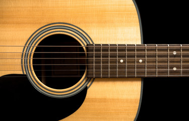 Yellow acoustic wooden guitar on a black background