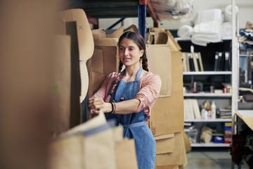 Female Worker Selecting Cardboard Papers In Sofa Workshop