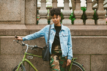 Young woman in camo pants standing with bike