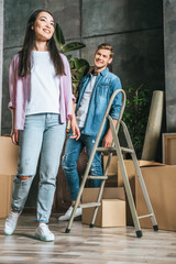beautiful young couple with boxes and ladder moving into new home