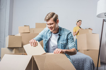 young couple unpacking boxes while moving into new home