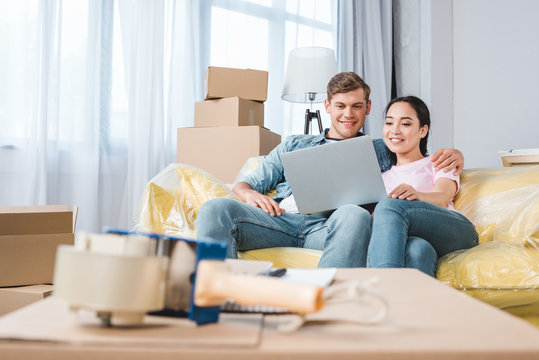 beautiful young couple using laptop on couch while moving into new home