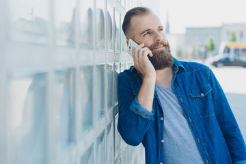 Bearded man leaning on a wall chatting on a mobile
