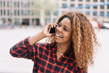 Delighted young African woman chatting on a mobile