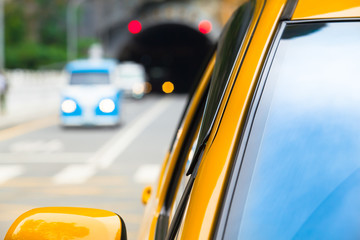 Driving Through Dark and Light / Closeup front window of yellow car and blurred traffic behind at...