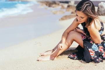 Young woman daydreaming and playing with sea sand