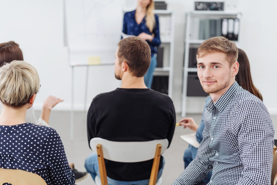 Young man smiling at camera during office meeting